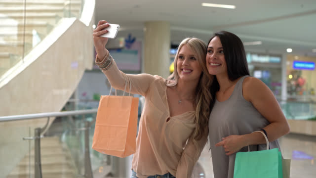 Tilt view of happy friends taking selfies in the mall