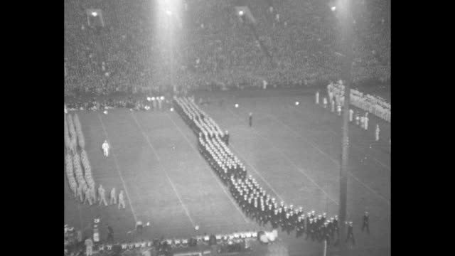 vídeos de stock, filmes e b-roll de tilt view of rows navy men marching during intermission / in soldier field spectators including some in navy uniforms facing right / l to r dave... - 1941
