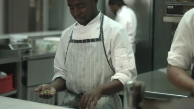 MS TILT_Chef sorting peas in open kitchen, at restaurant