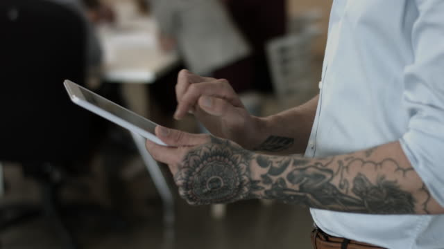 cu tilt_tattooed businessman scrolling on tablet - tattoo stock videos & royalty-free footage