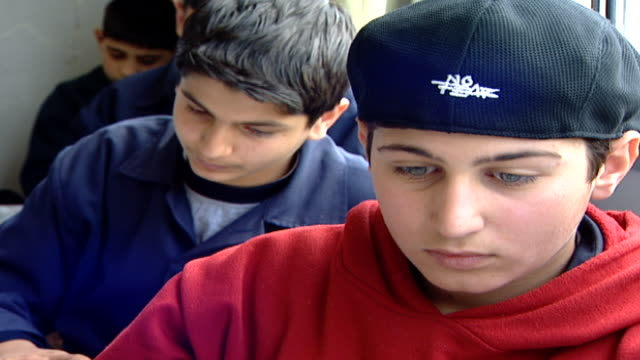 vidéos et rushes de tilt-down from a student with striking blue eyes, wearing a no-fear cap, to his textbook. irfan is a druze religious school with five branches in... - casquette de baseball