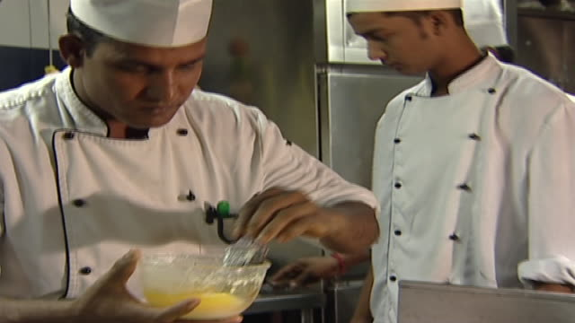 tilt-down from an indian chef brushing a roomali dish with egg wash while spinning it on a tandoor or coal-fired oven. roomali is a flatbread popular... - ingredient stock videos & royalty-free footage