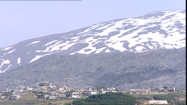 stockvideo's en b-roll-footage met tilt-down from snow-capped mount hermon which straddles the border between syria and lebanon to a village perched on foothill. - benen gespreid