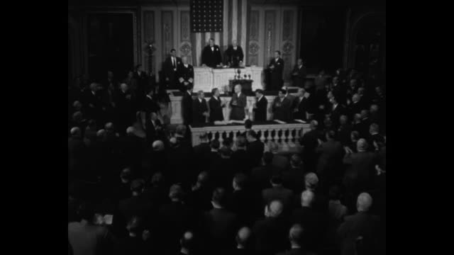 stockvideo's en b-roll-footage met tilt-down members of us congress applaud as fleet adm. chester nimitz and other us navy officials walk down aisle, approach speaker's platform in the... - 40 seconds or greater