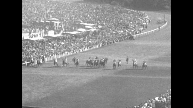 Tiltdown pan vast crowd with tents in the infield at Longchamp Racecourse / VS horses move from the starting line round curve into backstretch...
