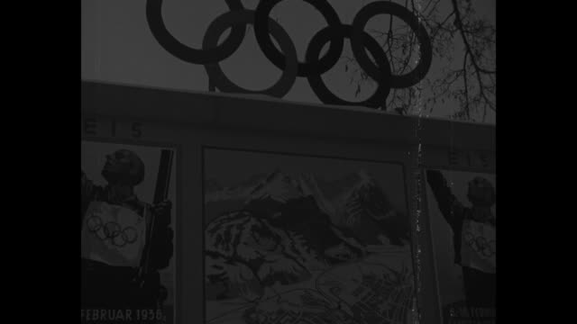 vídeos de stock, filmes e b-roll de tilt-down picturesque view of garmisch-partenkirchen, with crowds at winter olympics opening ceremony / sign features olympic rings with posters... - garmisch partenkirchen