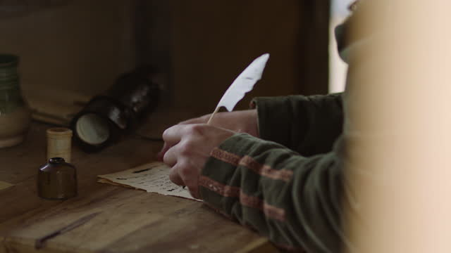 tilt-down reenactment shot of a man writing with a quill pen during the 17th century - 17th century stock videos & royalty-free footage