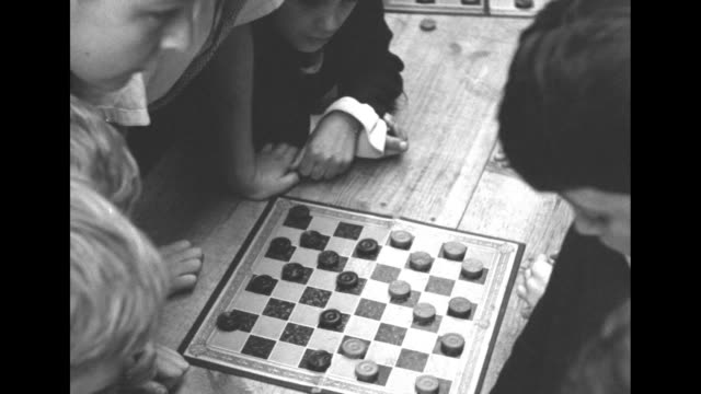 tiltdown shot checkerboard with game in progress children are gathered around the board one child reaches over and hits a boy that boy and the hitter... - table tennis bat stock videos & royalty-free footage