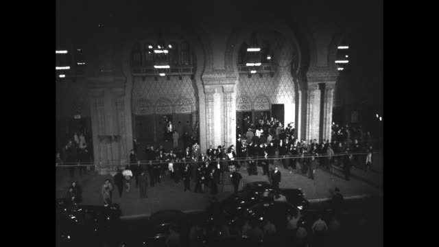 vídeos de stock, filmes e b-roll de tiltdown shot ext shrine auditorium where 19th academy awards ceremony will be held cars drive by small crowds on sidewalk / pov ext shrine... - shrine auditorium
