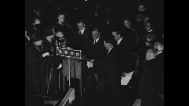 tilt-down shot franklin roosevelt, standing at podium, takes oath of office as he assumes the governorship of the state of new york, with his wife... - 長点の映像素材/bロール