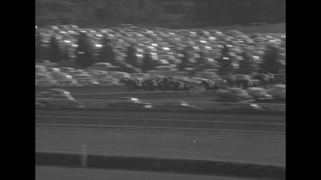 tilt-down shot horses enter racetrack at arlington park for the arlington classic stakes race / horses race in backstretch with parking lot full of... - enclosure stock videos & royalty-free footage