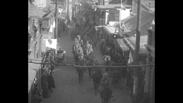 tilt-down shot japanese soldiers march in city street of chinchow after taking the city during their invasion of manchuria; japanese flags, some... - 満州地方点の映像素材/bロール