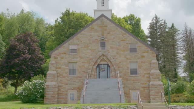 vídeos de stock e filmes b-roll de tilt-down shot of the front side of the community presbyterian church - pináculo campanário