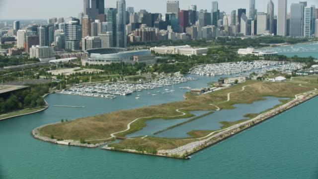 vídeos de stock e filmes b-roll de tilt-down shot of the northerly island with downtown chicago in the background - aquário john g shedd