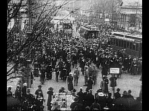 Tiltdown shot people in streets with trolley cars stopped nearby / long pan shot very dense crowd in street with soldiers interspersed / soldiers and...