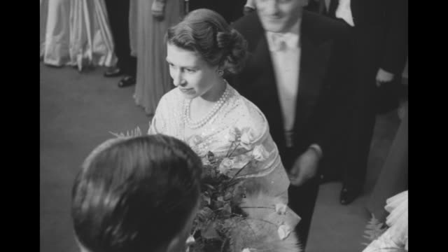 tiltdown shot princess elizabeth and princess margaret holding bouquets smile and greet celebrities in a line at the command performance of the... - 1949 stock videos and b-roll footage