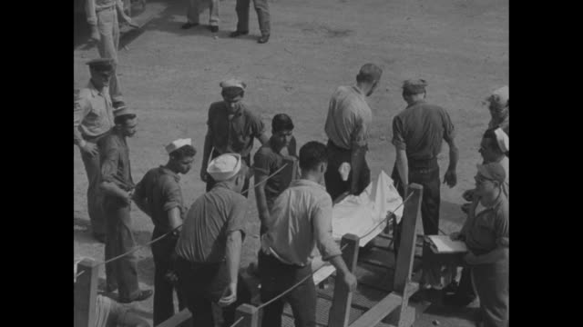 tilt-down shot wounded servicemen on stretchers are brought down gangplank of hospital ship uss solace by sailors; other sailors put wounded men into... - red cross stock videos & royalty-free footage