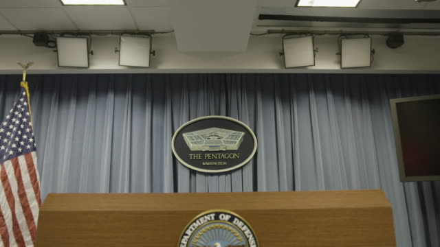 tilt-down to pentagon auditorium podium and department of defense insignia - ministero della difesa video stock e b–roll
