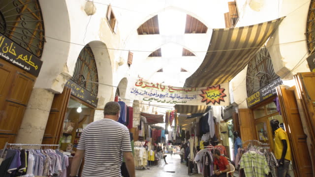 tiltdown to the tailors' souk in tripoli's medieval market a shopkeeper sits outside his shop waiting for customers a banner advertises men's clothing - religiöse kleidung stock-videos und b-roll-filmmaterial