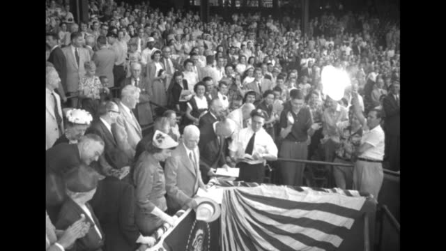 Tiltdown MS US Pres Dwight Eisenhower and others in the stands at Griffith Stadium during the Congressional Baseball Game / team players crowded...