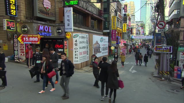 tiltdown zoomin on busy sidewalk in seoul south korea uniformed workers and pedestrians walk down street street is lined with signs advertisements... - korean ethnicity stock videos & royalty-free footage