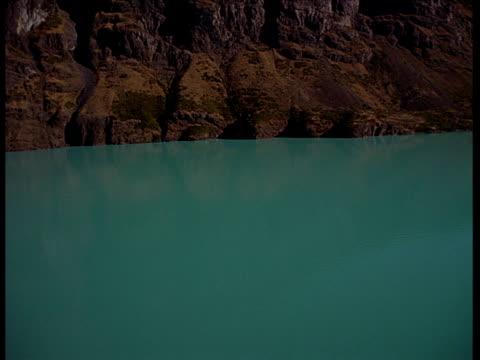 stockvideo's en b-roll-footage met tilting aerial track over glacial lake, shore and reflected sun - ruimte exploratie