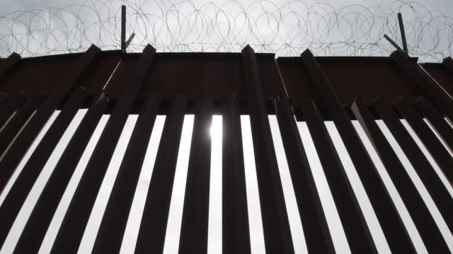 vídeos de stock e filmes b-roll de tilting down and pulling back dolly shot of the sun peeking through the steel-slat border wall (on the us side) between mexico and the united states topped with razor wire on a partly cloudy day - muro circundante