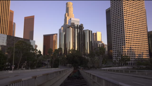 vídeos de stock, filmes e b-roll de tilting down from the downtown los angeles skyline to the 110 freeway at sunset - tower
