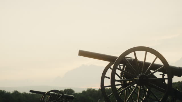 tilting down shot of a several us civil war cannons from gettysburg national military park, pennsylvania on a hazy day at sunset - gettysburg stock videos & royalty-free footage