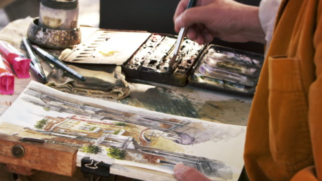 Tilting down shot of artist painting using watercolors a scene of a gondola on a canal in Venice.