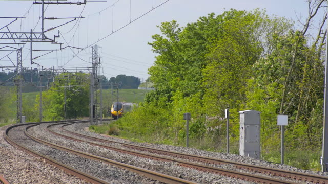 A Tilting passenger train traveling at speed rounds a curve on the West Coast mainline