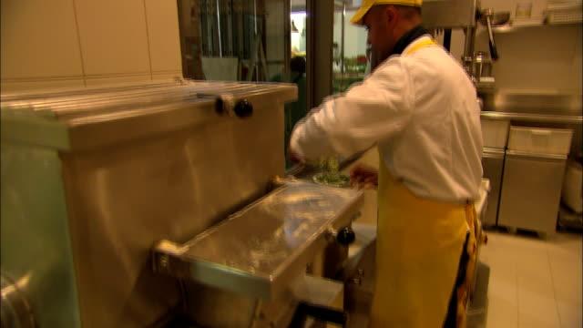 Tilting shot of a man using a pasta machine