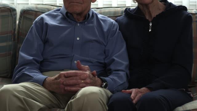 tilting shot of a senior couple in a living room. - ernst stock-videos und b-roll-filmmaterial