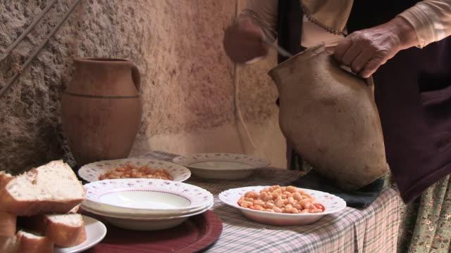 vídeos y material grabado en eventos de stock de tilting shot of an older woman serving a bean dish. - camisa blanca