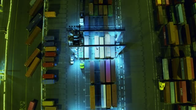 tilting top down aerial view of straddle carrier moving cargo containers in port - straddle carrier stock videos & royalty-free footage