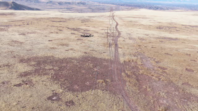 tilting up aerial view of a hexacopter drone inspecting power lines above a grassy field with a dirt road underneath and mountains outdoors in the background in the grand valley of western colorado - examining stock videos & royalty-free footage
