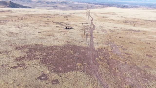 vídeos de stock, filmes e b-roll de inclinando-se a vista aérea de um zangão de hexacopter que inspeciona linhas eléctricas acima de um campo gramíneo com uma estrada da sujeira embaixo e montanhas ao ar livre no fundo no vale grande de colorado ocidental - hélice peça de máquina