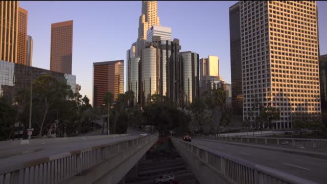 vídeos de stock, filmes e b-roll de tilting up from the 110 freeway to the downtown los angeles skyline at sunset - torre estrutura construída