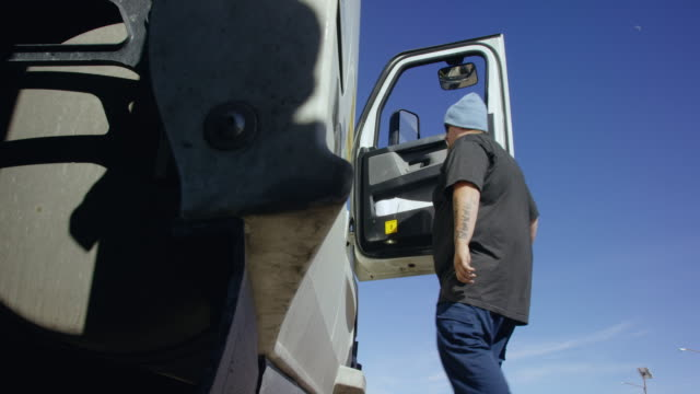 """tilting up shot of a caucasian male truck driver in his thirties demonstrates the proper use of the """"three points of contact"""" technique for climbing into the passenger side of his semi-truck and closing the door in the high desert of utah on a sunny day - balance stock videos & royalty-free footage"""