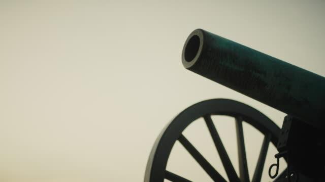 tilting up shot einer us-bürgerkriegskanone aus dem gettysburg national military park, pennsylvania bei sonnenuntergang - gettysburg stock-videos und b-roll-filmmaterial