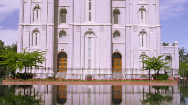 tilting up shot of the front of the lds salt lake temple from a reflecting pool. - mormonism stock videos & royalty-free footage