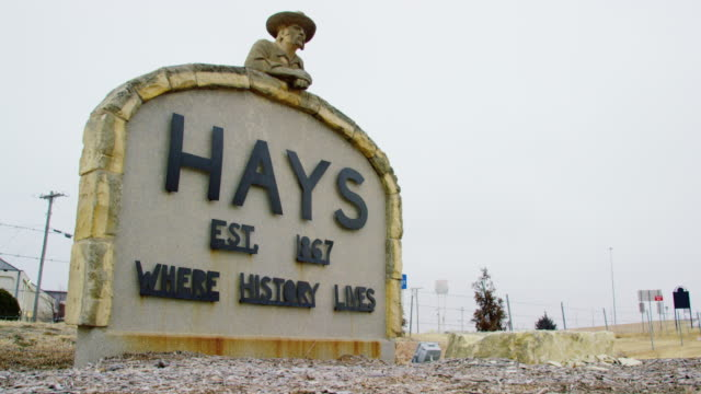 """tilting up shot of the sign entering the town of hays, kansas (""""hays, est. 1967, where history lives"""" - cowboy hat stock videos & royalty-free footage"""