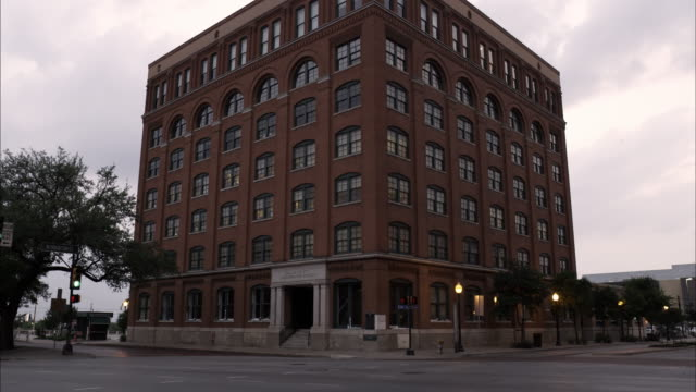 stockvideo's en b-roll-footage met tilting up shot of the texas school book depository at dealey plaza, dallas. - school building