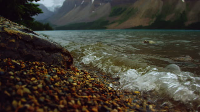vídeos y material grabado en eventos de stock de tilting up slow motion shot of waves from a mountain lake lapping against the shore con las montañas rocosas canadienses en jasper national park under an overcast sky in alberta, canadá - jasper