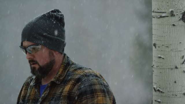 tilting up wide shot of a caucasian man in his thirties with a beard cutting a wooden aspen log with a chainsaw on a snowy winter day - cappotto invernale video stock e b–roll