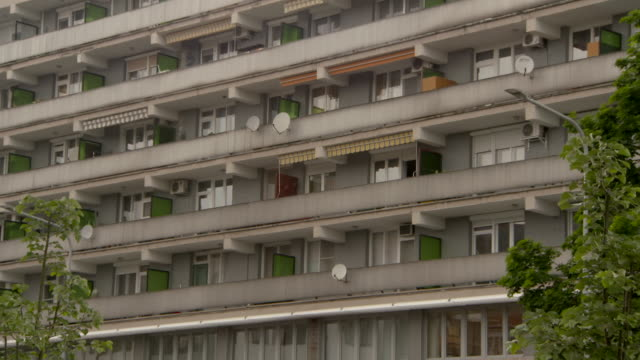stockvideo's en b-roll-footage met tilt-pan: colorful balconies on a large cement apartment complex - gevel