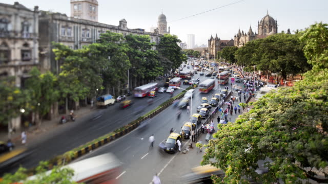 vídeos de stock, filmes e b-roll de tl, ws, ha, tilt-shift, crowds and traffic pass victoria terminus railway station / mumbai, india - time lapse de trânsito