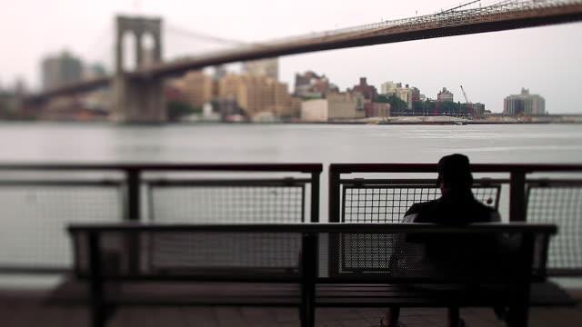 Tilt/shift man sitting on bench with Brooklyn bridge in background