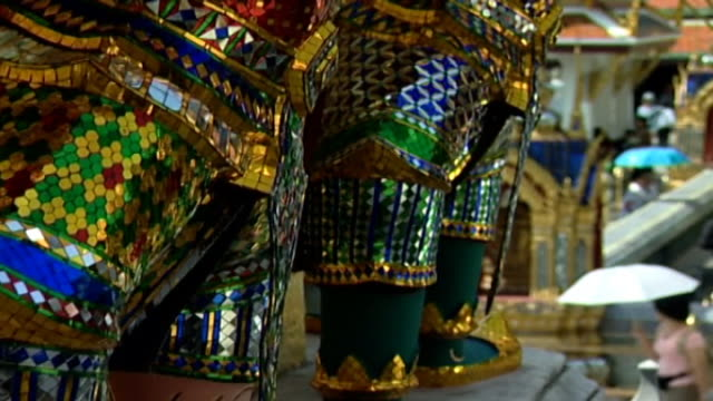 tilt-up across demon statues at the base of a golden chedi, or spire. the statues are covered with sparkling glass mosaics. - spire stock videos & royalty-free footage