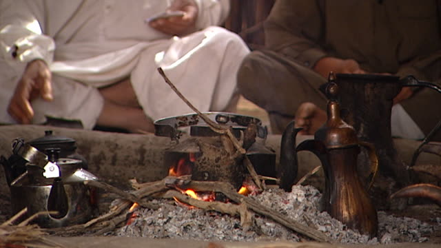 tiltup from a coffee pot on an open fire in a mudhif to an elderly marsh arab mudhif architecture dates back to sumerian times - coffee pot stock videos & royalty-free footage